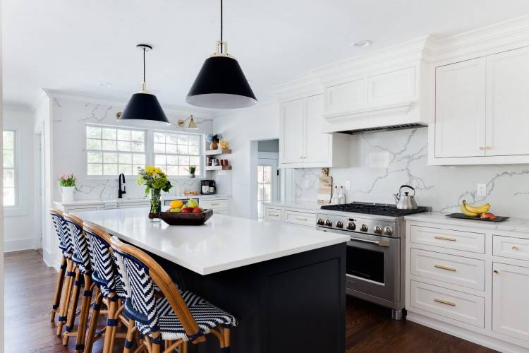 The white of the  countertops contrasts beautifully with the black stained cabinets