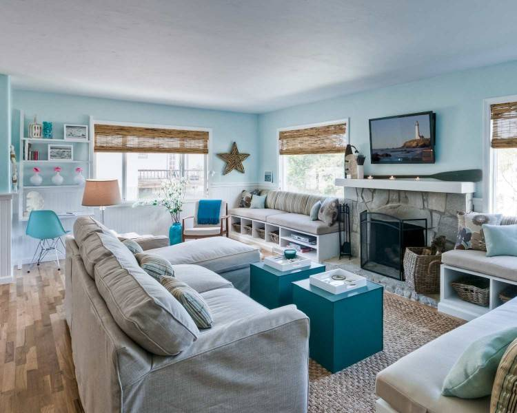 Blue beach style accent chairs in a cottage living room add a subtle charm  next to white slip covered sofas under an oak plank ceiling