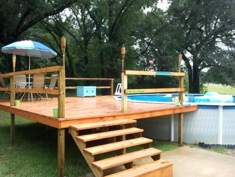 A nice wooden deck built around a semi inground pool