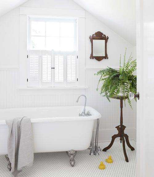 Chic white cottage bathroom boasts vertical white shiplap walls accented  with a gold ornate mirror above a white shaker vanity fitted with a gray  marble