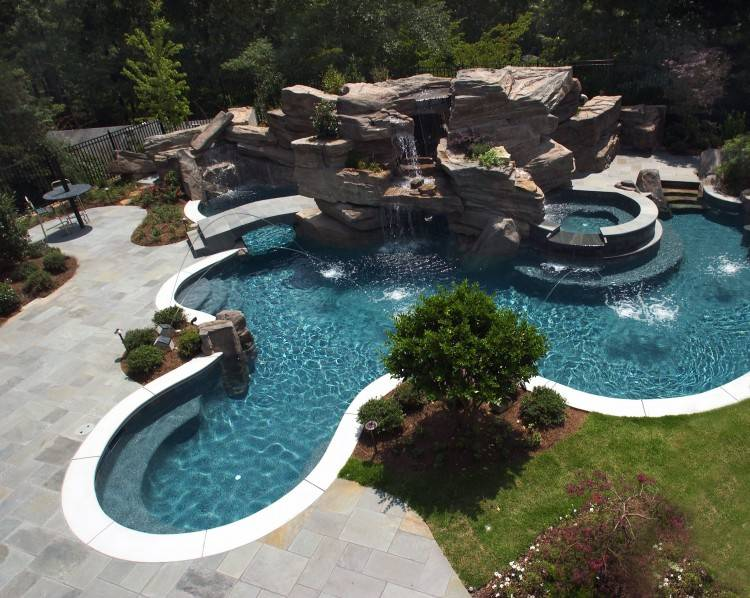 Elaborate Swimming Pool featuring Large grotto, waterfall and tube slide