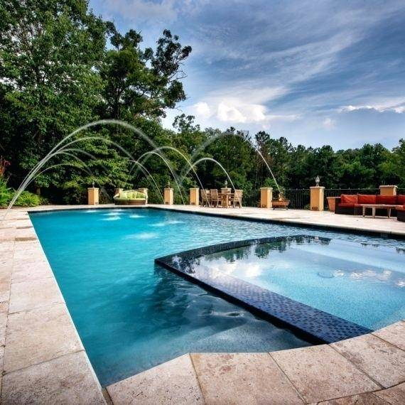This natural swimming pool design features a raised spa, sun shelf and  water slide