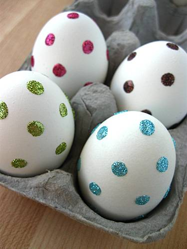 Drop small amounts of liquid food color onto hard cooked eggs splashed with  white vinegar