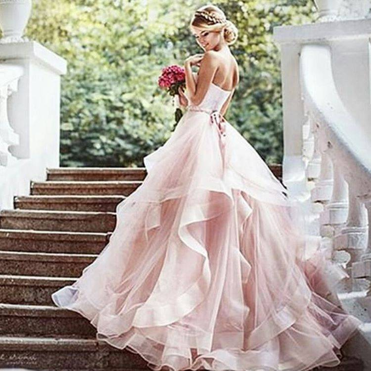 ,Soft pink bridesmaids' dresses that look magical on  that green scenery