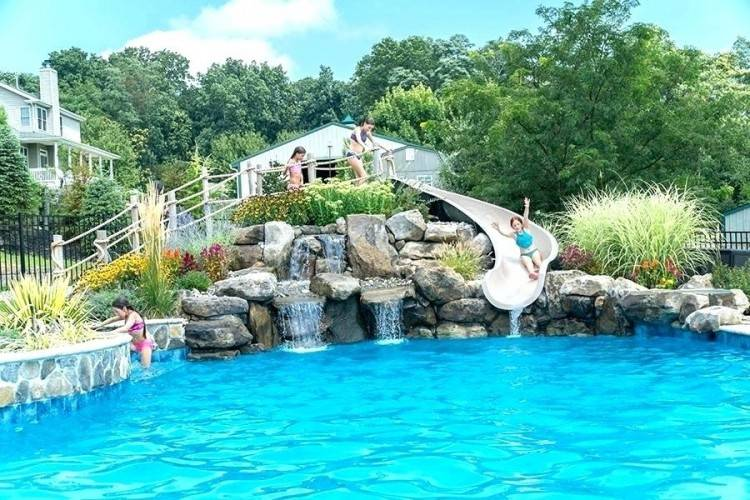 Tropical pool, spa, waterfall, slide, and grotto carved in artificial rock