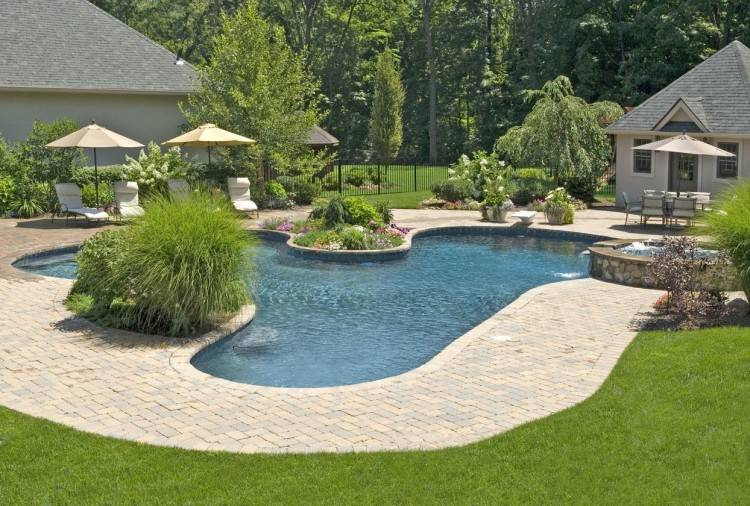 Arial view of a large backyard pool with raised deck off to the side