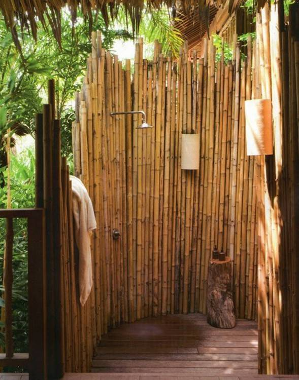 An exotic tropical outdoor shower surrounded by lush gardens and bamboo  walls is ideal for resort living