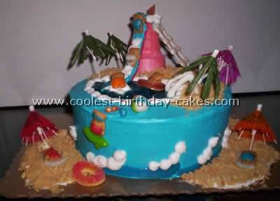 Three tier white wedding cake decorated with purple, blue and green  seashells and decorations